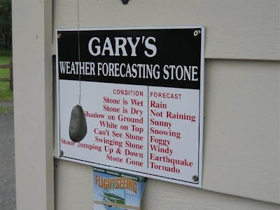 photo of a rock hung by a string in front of a weather forecasting sign..if rock is wet...raining