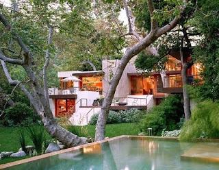 Piscina y la casa en el jardín con árboles