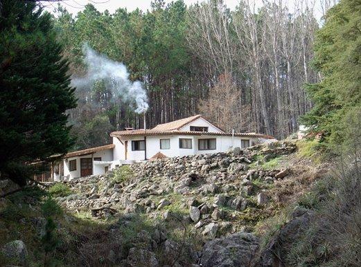 Vista exterior de la cabaña rústica hecha de piedra, troncos y mampostería