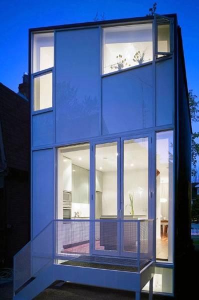 Vista trasera de la casa iluminada desde el interior