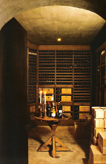 Wine cellar with tasting table in center and wine crates and rows of wine, Timeless Interiors by Axel Vervoordt, edited by lb for linenandlavender.net (l&l)