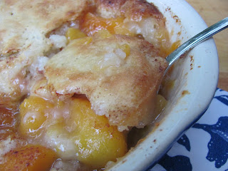 A close up of peach cobbler in a white dish