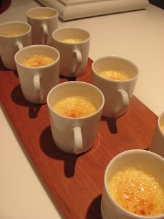 A close up of finished coconut creme brulee in mugs on a wooden board
