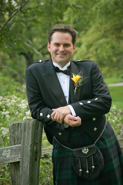 Jonathan leaning on fence at Lapham Peak State Park in Scottish wedding attire