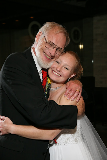 Bride and dad hugging and smiling at wedding reception