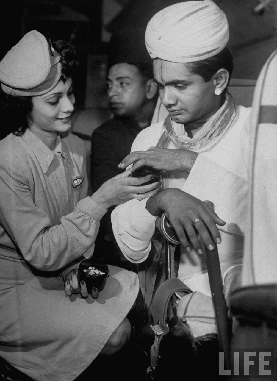 Air India flight attendant Monica Gilbert (L) passing out spices to Madrasi Brahmin passenger during trip across India.