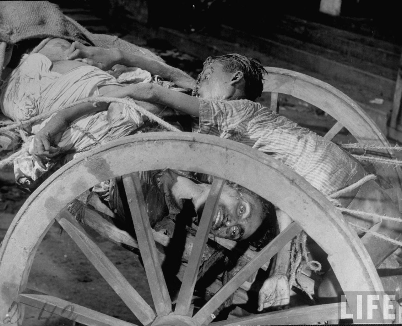 Corpses lying in a cart on their way to be cremated after bloody rioting