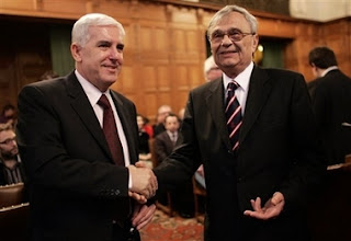 Bosnian agent Sakib Softic, left, shakes hands with Head of the Law Council of the Ministry of Foreign Affairs of Serbia and Montenegro Radoslav Stojanovic at the International Court of Justice, also known as the World Court, in The Hague, the Netherlands, Monday Feb. 26, 2007. The United Nations' highest court began delivering a historic ruling Monday on whether Serbia is responsible for genocide through the killing, torture, rape and expulsion of Bosnian Muslims. It is the first time an entire nation is being held to judicial account for the ultimate crime.