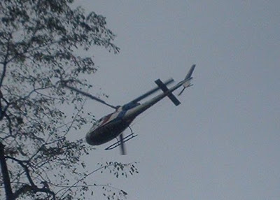 helicopter flying above marchers