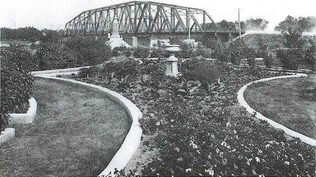Early 1920s photo of WWI memorial (in background) and flower beds