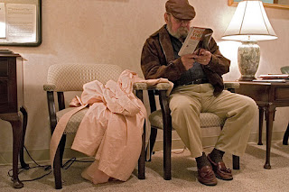 man reading in a doctor's waiting room; woman's coat on the next chair