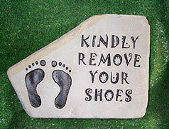stone with carving - picture of feet, and the words kindly remove your shoes