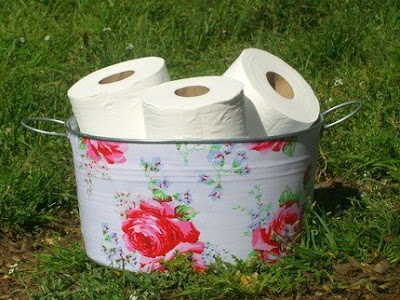 flowered bucket holding toilet paper rolls