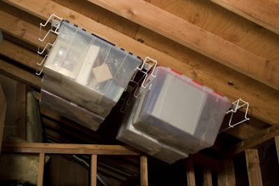 rack holding two large plastic boxes in rafters