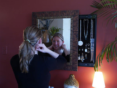jewlery case behind a mirror - partly open, with woman looking in the mirror