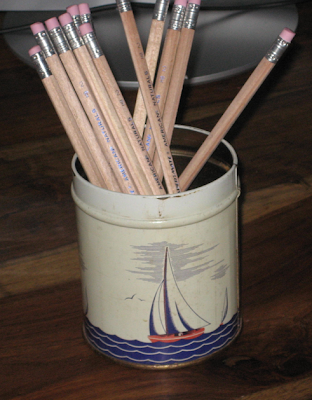tin with picture of sailboat, holding pencils