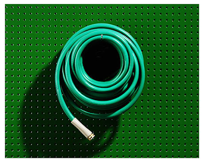 green pegboard with hose