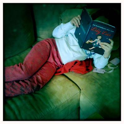 Foto von einem Kind auf dem Sofa mit dem Kopf im Buch Die wunderbare Welt der Lily Lux