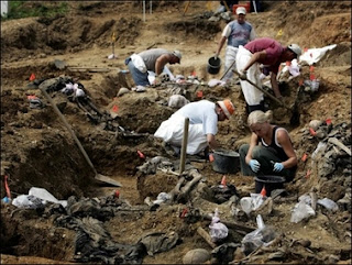 A forensic expert works in a mass grave in the village of Budak just outside Srebrenica in 2005