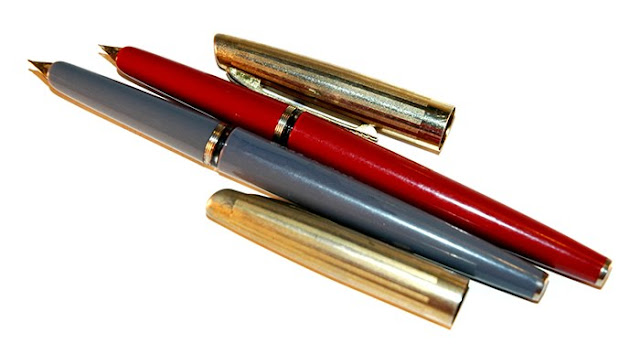 free stock photo of old foundtain pens - one in red, one in gray, both with gold tone caps