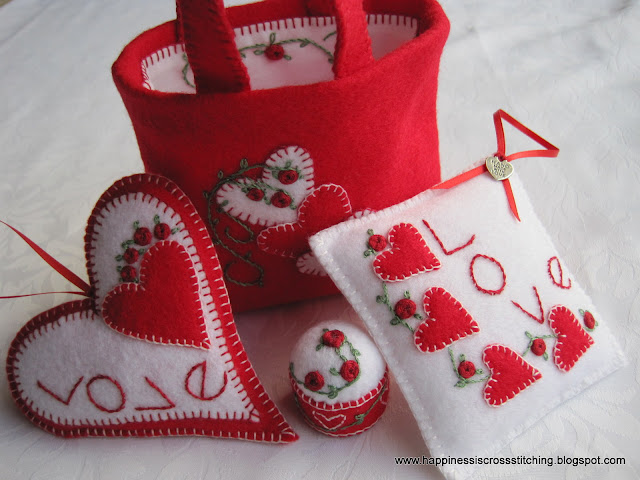 Felt loveheart ornament, square pillow, bottle cap pincushion and small felt bag decorated with red roses and lovehearts