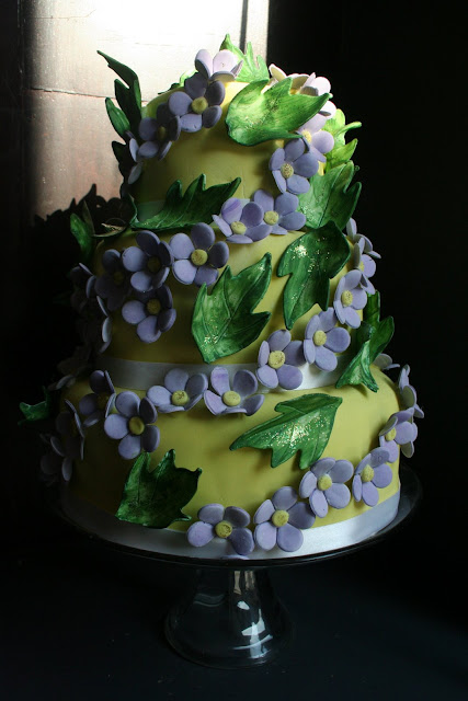 wedding cake was garlanded with mauve violets and green ivy