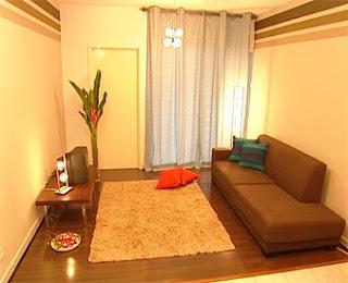 Ruang Tamu Tipikal Set Sofa Yang Bulky Dalam Corak Busy Dan Sebuah Shelf Display Untuk Tv Radio Crowded Kesemuanya Memberikan Penataan