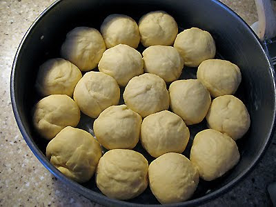 A close up photo of partybrot dough balls in a buttered pan.