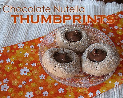 A close up photo of three chocolate Nutella thumbprint cookies on a clear plate.
