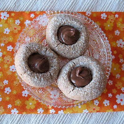 An overhead photo of three chocolate Nutella thumbprint cookies on a clear plate.