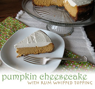 A slice of pumpkin cheesecake with rum whipped topping resting on a plate with the whole cheesecake in the background.
