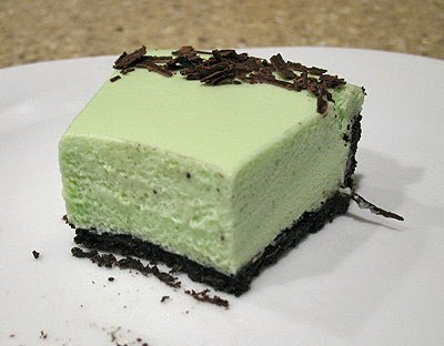 A close up photo of a half eaten slice of grasshopper pie on a white plate.