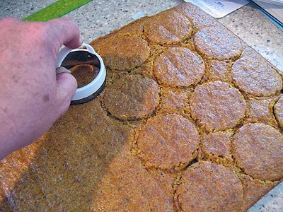 A close up photo of circles being cut out of the carrot cake sheet with a 2-in round cutter.