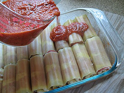 A close up photo of sauce being poured over manicotti with prosciutto in a baking dish.
