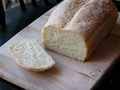 A photo of a simple one hour homemade bread loaf with a slice removed.