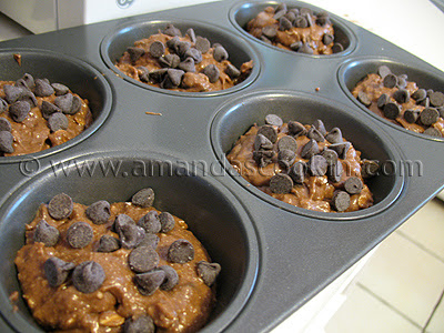 A close up photo of muffin pan filled with chocolate chocolate chip muffin dough.