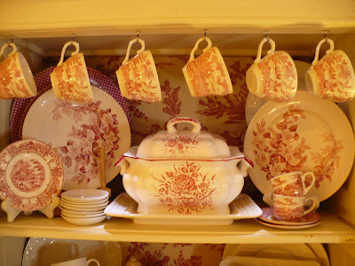 red transferware dishes in a cabinet