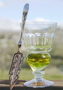 A reservoir glass filled with a naturally colored verte absinthe next to an absinthe spoon.